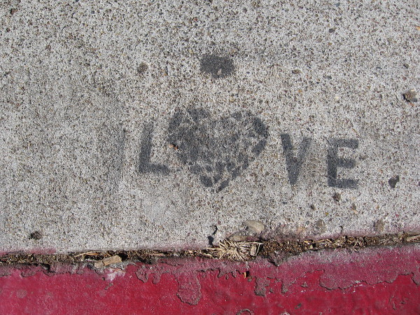 Someone stenciled LOVE on the sidewalk.