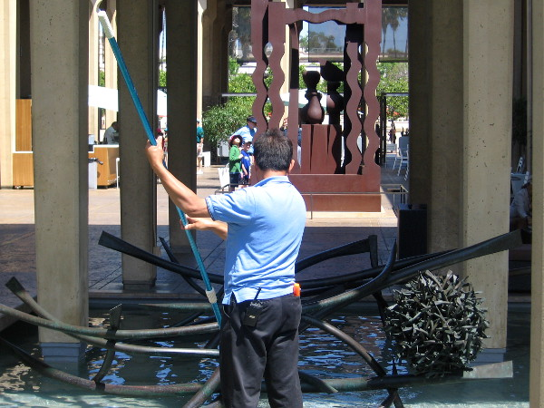 Man cleans pool of water in San Diego Museum of Art's Sculpture Court.