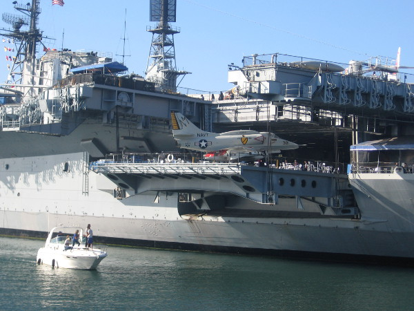 Small boat passes near USS Midway aircraft carrier on San Diego Bay.