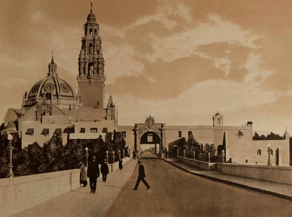 Photograph of the Panama-California Exposition's La Puerta del Oeste (west entrance) taken from Cabrillo Bridge. Dome and bell tower of the California State Building rise into the San Diego sky.