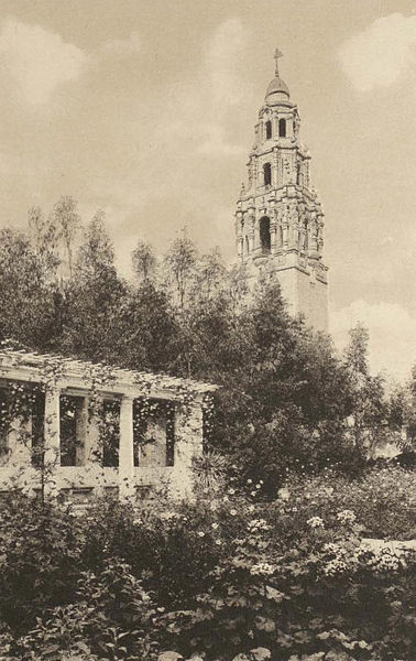 View of shady pergola and the iconic 208 feet tall California Tower from Los Jardines de Montezuma (Montezuma Gardens) in 1915.