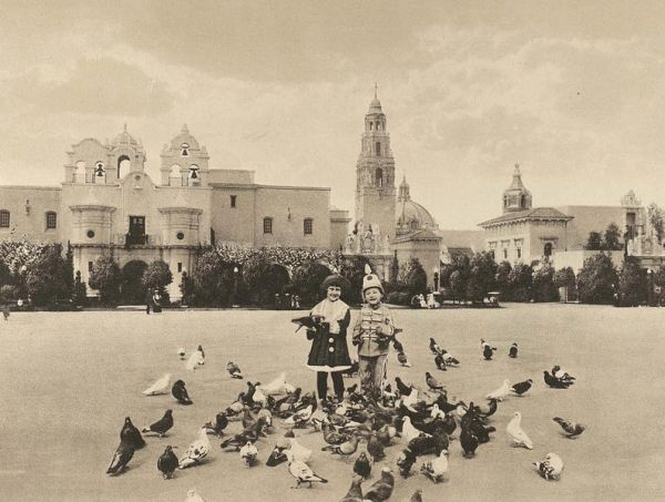 Kids feed pigeons on the central Plaza de Panama. The Indian Arts Building with mission bells on left was renamed House of Charm and reconstructed in 1996. It now contains the Mingei Museum.