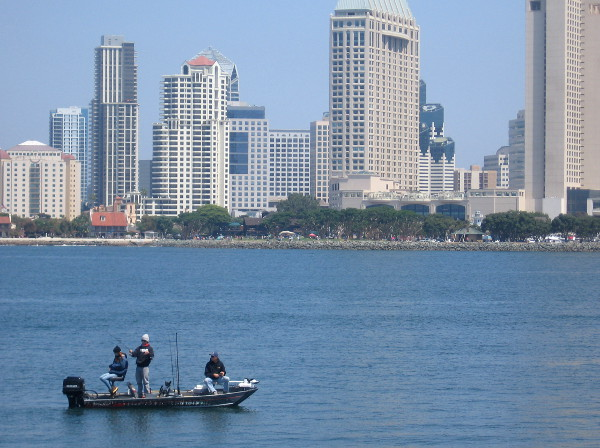 Fishermen enjoy a day on San Diego Bay with downtown skyline in background.