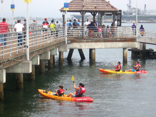Kayakers paddle under the Coronado Ferry Landing pier.