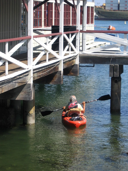 Kayaker checks out the water underneath Joe's Crab Shack.