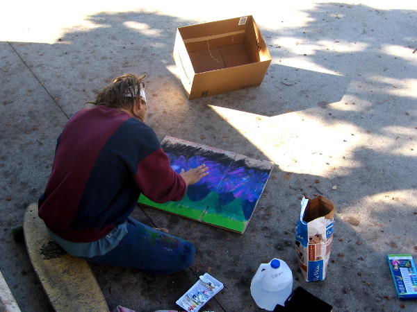 Young man with skateboard paints for donations on a San Diego sidewalk.