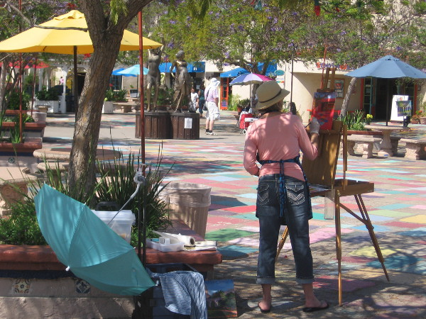 An artist in Balboa Park's Spanish Village works on a canvas in the colorful courtyard.