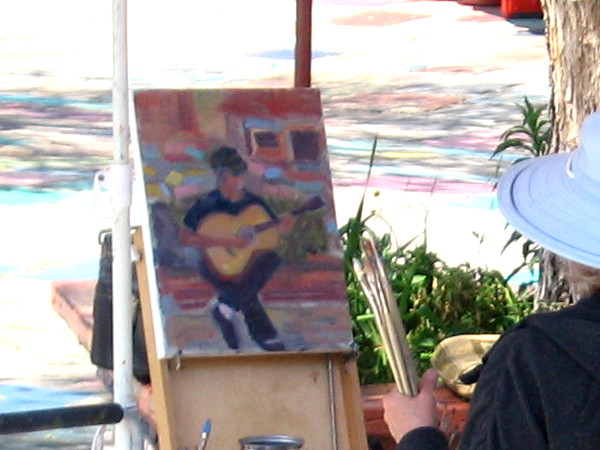 A painted guitarist seems to emerge from sunny San Diego dappled brightness.