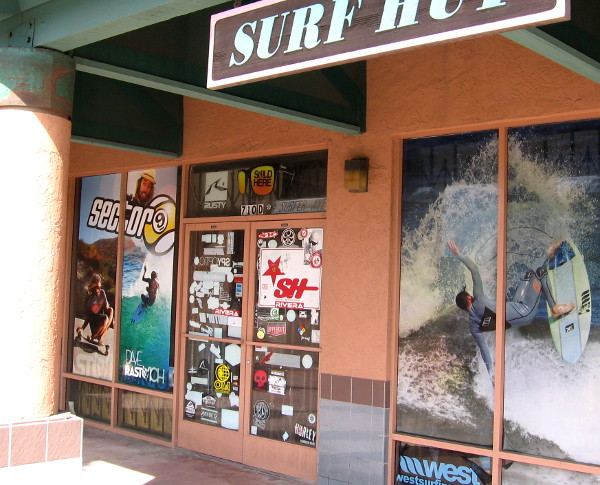 Imperial Beach surf shop has a door plastered with beach-themed decals and signs.