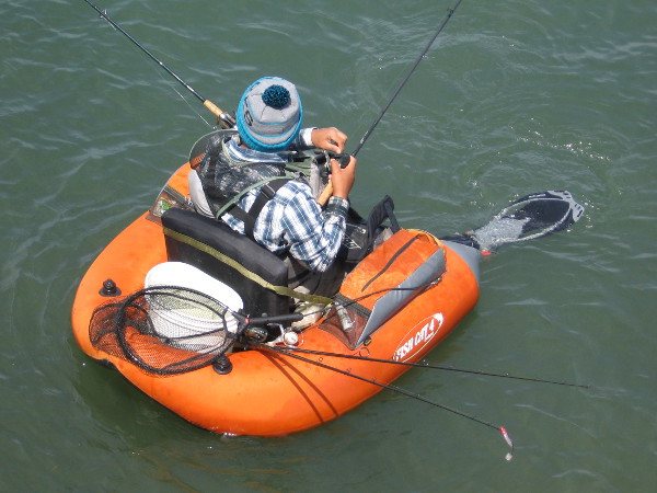 Guy in small inflatable with bucket, net and fishing rods hopes to catch something.