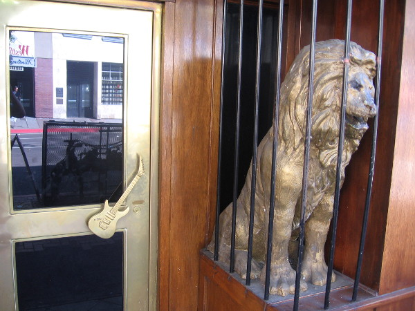 Caged lion in the Gaslamp guards the Hard Rock Cafe, and a door with electric guitar handle.
