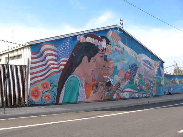 Fun mural in Barrio Logan shows flag, kids, fruit, a train and birds.