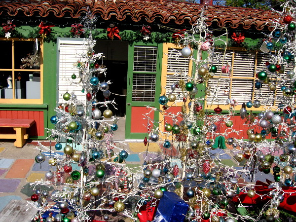 An artist studio in Spanish Village behind many very colorful Christmas trees.