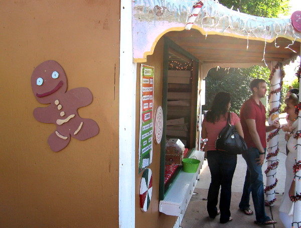 Gingerbread house in organ pavilion sells Christmas treats to the growing crowd.