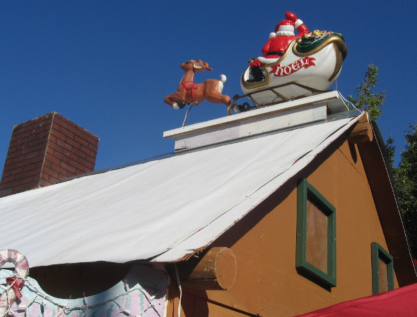 Santa Claus has landed with his little reindeer on a rooftop!