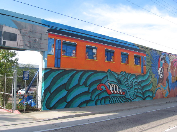 San Diego Trolley travels through a scene similar to those found in nearby Chicano Park.