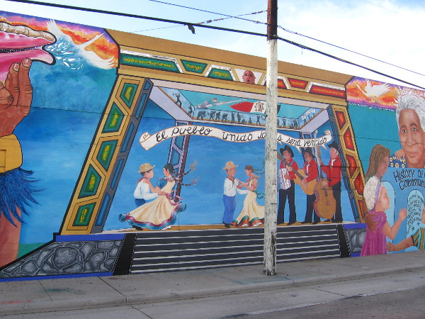 Nearby Chicano Park's pavilion is shown with lots of folks dancing.