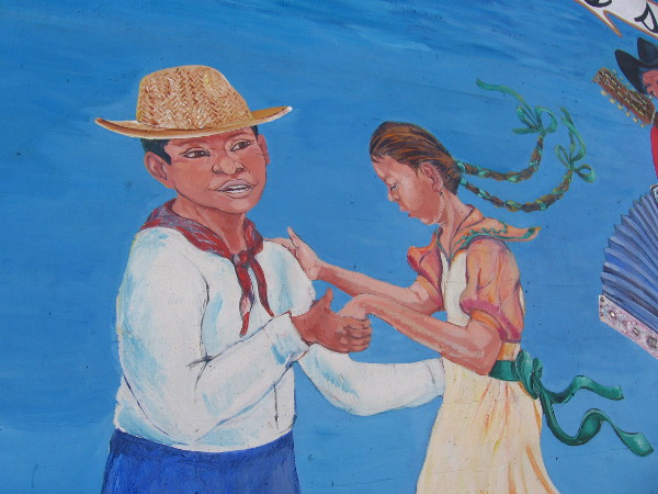 Young man and lady dance on the festive outdoor mural.