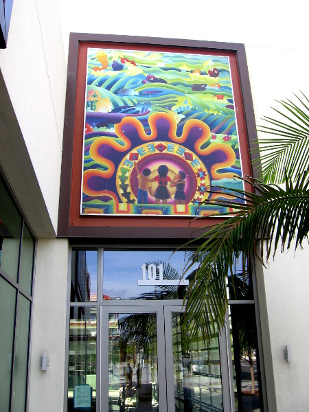 Colorful art above a store's glass door.