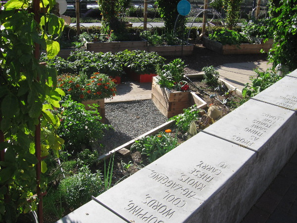A whimsical poem is inscribed on a long wall enclosing the small garden.