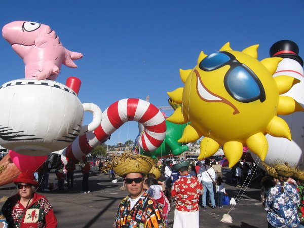Balloons of every color and shape bob and rise above the gathering handlers.