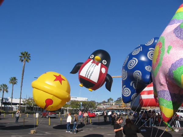 Balloons fill the blue sky, and so does a penguin in a tuxedo.