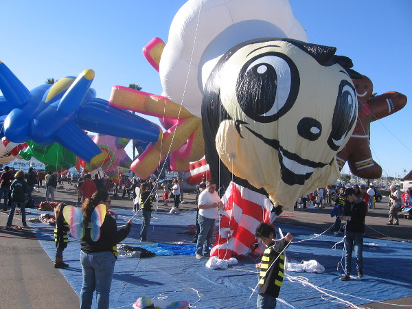 Happy bumble bee billows as it's filled with helium in parade staging area.