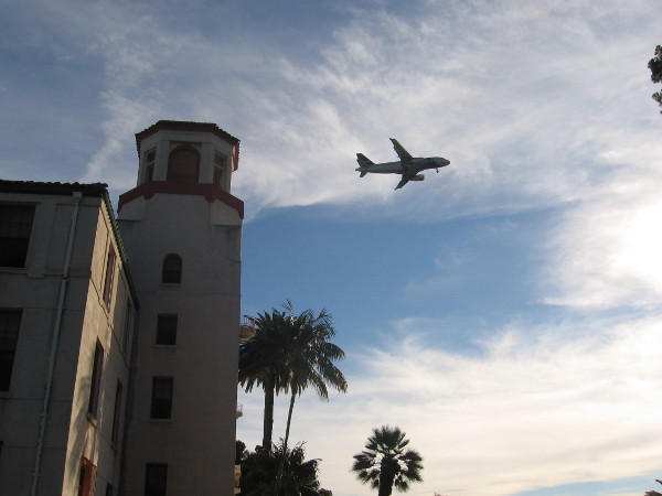 Plane approaching Lindbergh Field flies above Balboa Park Administration Building.