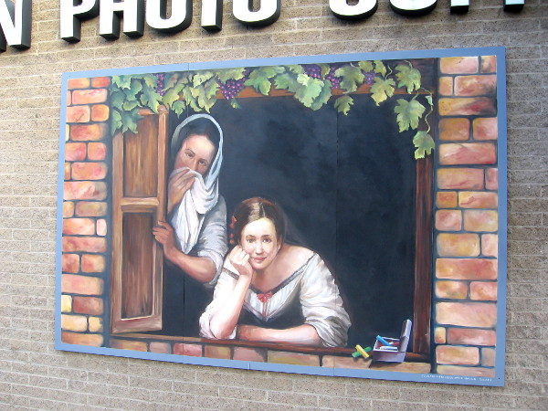 Two people gaze from painted mural window in Little Italy.