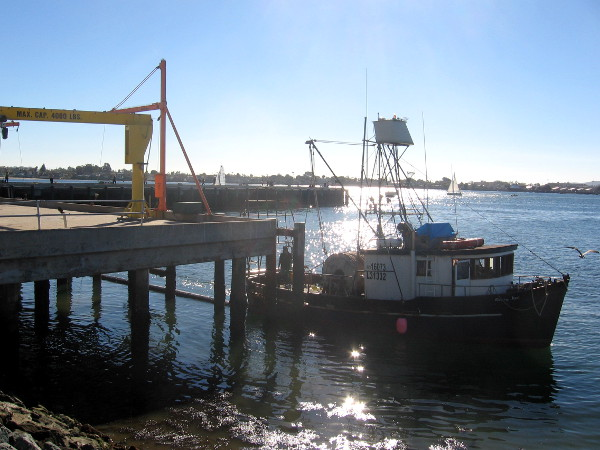 Fishing boat passes by the dock and crane.