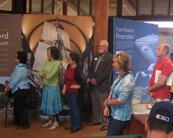 People listen to presentation at opening of Yankee Baleeiros whaling exhibit.