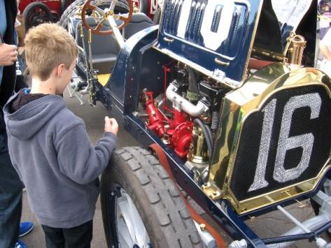 Kid checks engine of vintage car at Balboa Park show commemorating 1915 race.