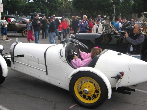 News cameraman gets a shot of young girl in pink pretending to race a vintage car.