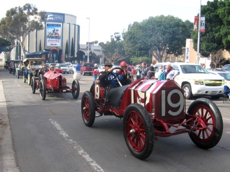 A long line of beautiful vintage hundred-year-old autos rumbles past.