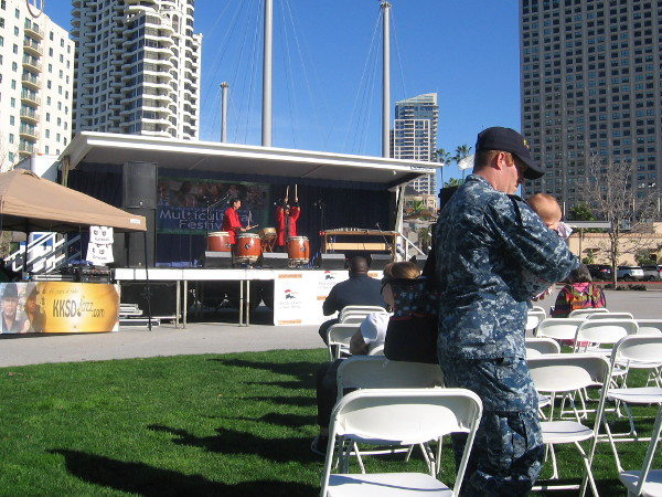 Serviceman with small child enjoys a sunny day at the Multicultural Festival in San Diego.