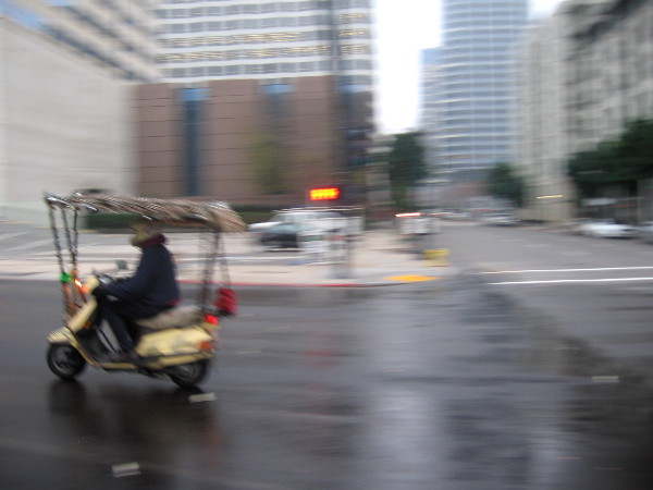 Scooter with fringed canopy zooms past as I swing my camera to capture a sudden morning photo.