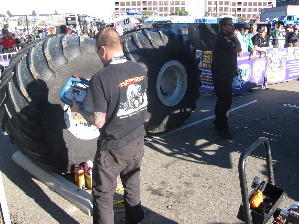 Mechanic guy near a couple of gigantic spare tires.