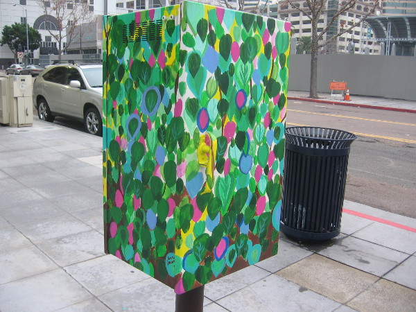 Mysterious elevated box on the sidewalk is colorfully painted with leaves.