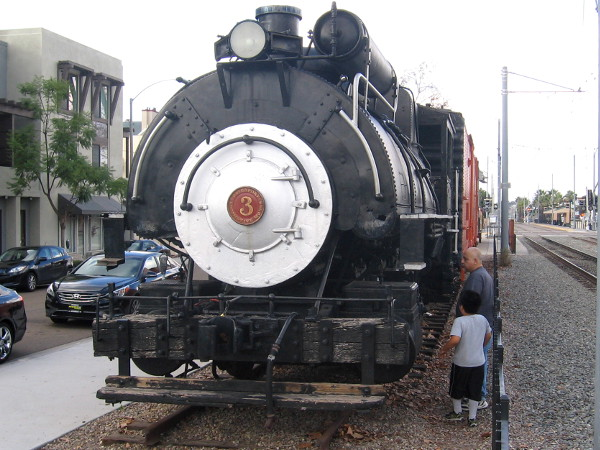 Dad and son check out old steam locomotive on display at La Mesa Depot Museum.