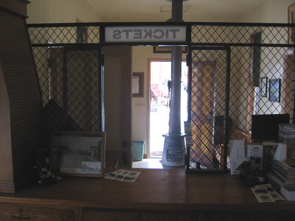 Looking out through ticket window at the tiny train depot waiting room.