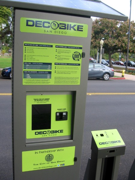 DecoBike bikeshare stations feature a touchscreen, instructions and a row of bike docks.