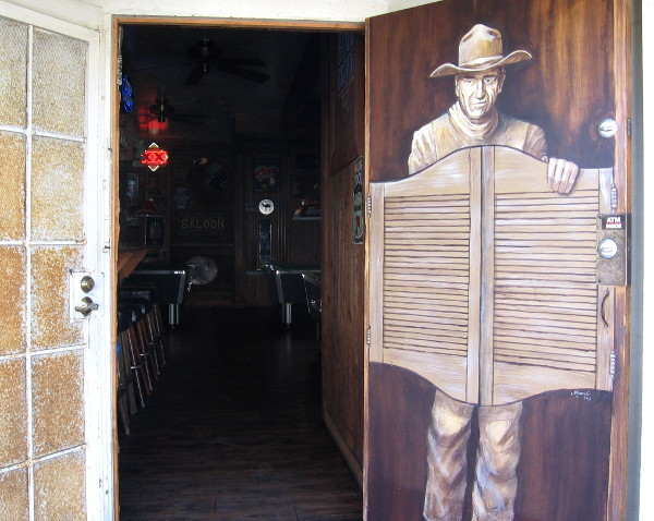John Wayne seems to be coming through a door of the Old Town Saloon.
