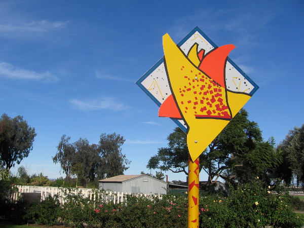 Odd, speckled sign stands beside Balboa Park's rose garden.