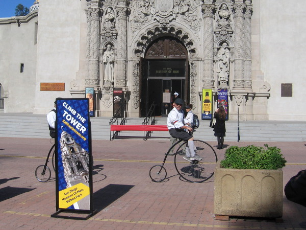 Several cool bicyclists happened to ride down El Prado in front of the Museum of Man.