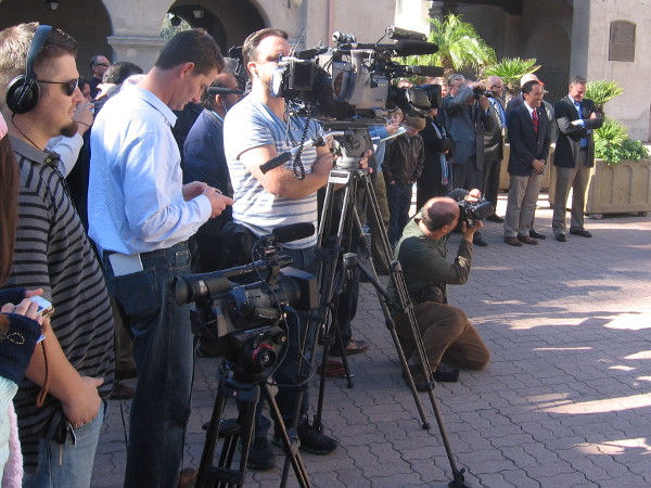News cameras wait for speeches, and so do the assembled dignitaries nearby.
