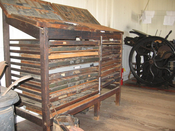 Drawers hold hand-set type that used to be used in old newspaper printing presses.