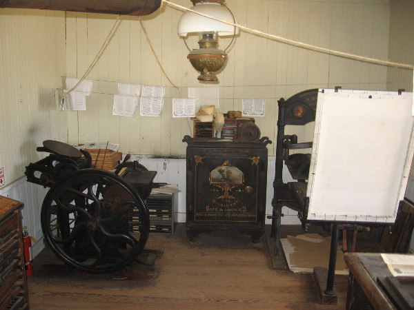 Massive Washington hand press can be glimpsed to the right in small printing shop.