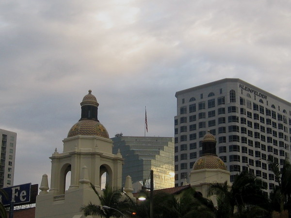 Sunlight reflects from silvery skyscraper beyond domes of the Santa Fe Depot.