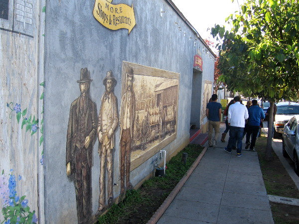 People walk past cool street mural near side entrance to Old Town Saloon.
