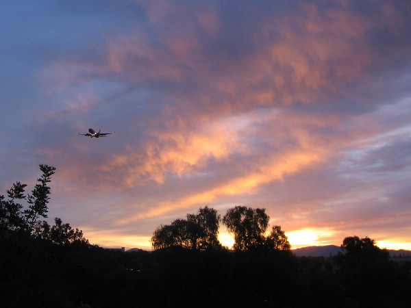Plane approaches San Diego International Airport high in sky during sunrise.